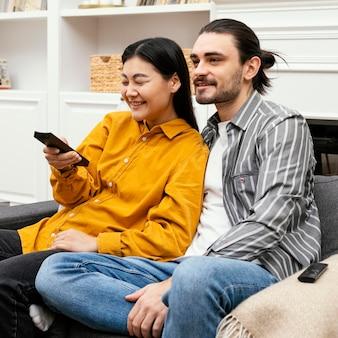 Para siedzi na kanapie przed telewizorem widok z boku