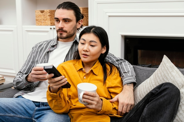 Para siedzi na kanapie przed telewizorem