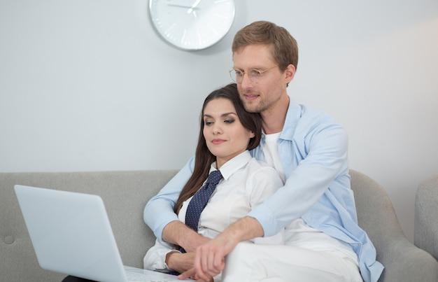 Para siedzi na kanapie przy użyciu laptopa. kobieta pracuje w domu, siedząc w ramionach chłopaka. mężczyzna nosi cienkie okrągłe okulary przytulanie żony od tyłu, podczas gdy ona pracuje na komputerze w domu na kanapie