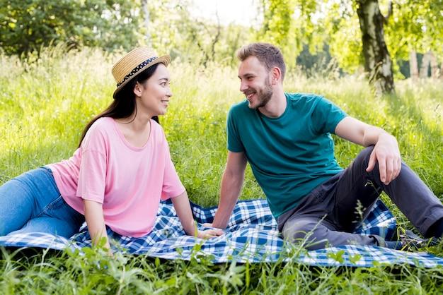 Para siedzi na kratę na pikniku