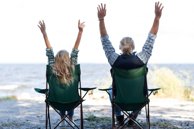 Para siedzi na krzesłach z rękami w powietrzu