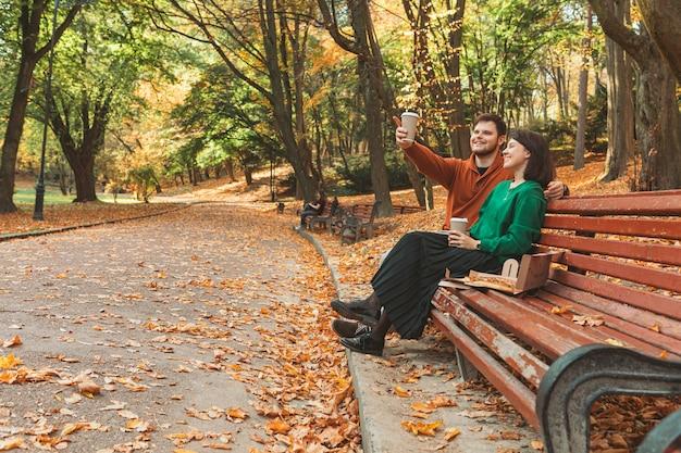 Para siedzi na ławce w parku publicznym w jesienny słoneczny dzień, wskazując na miejsce. pić na wynos