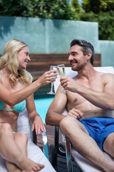 Para siedzi na leżaku i opiekania kieliszkiem szampana