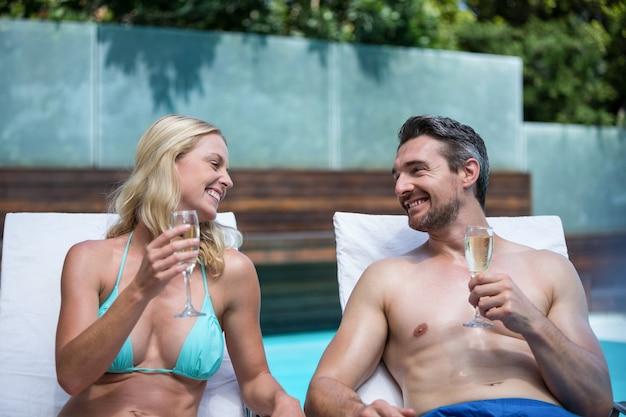 Para siedzi na leżaku o szampana