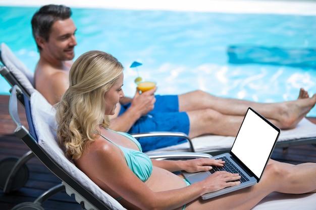 Para siedzi na leżaku przy basenie