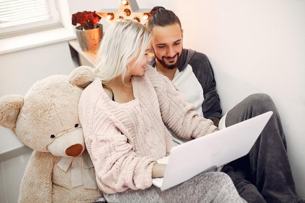 Para siedzi na łóżku w pokoju i korzysta z laptopa
