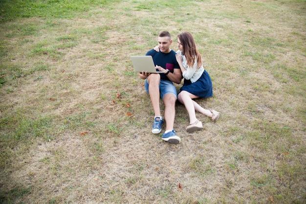 Para siedzi na trawie z laptopem