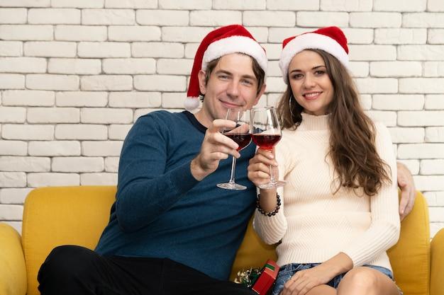 Para siedzi picie czerwonego wina na kanapie.