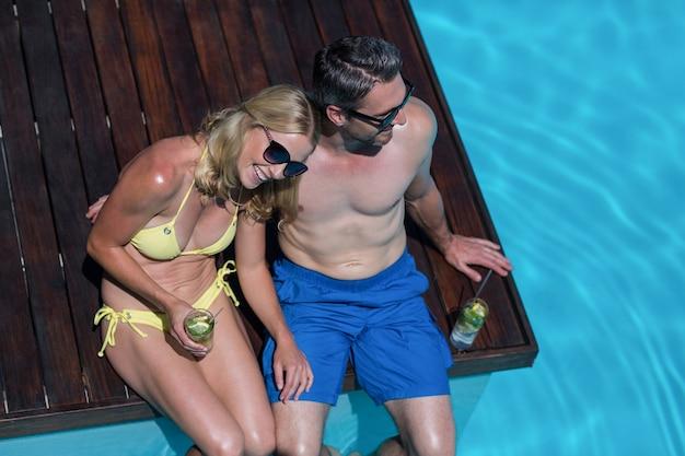 Para siedzi przy basenie z kieliszkiem mojito