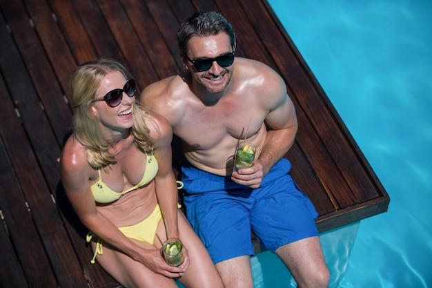 Para siedzi przy basenie ze szklanką mojito