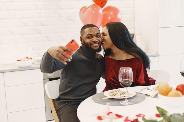 Para siedzi przy stole, jedząc posiłek, rozmawiając i śmiejąc się w walentynki