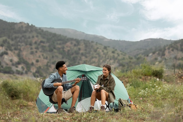 Para siedzi w pobliżu namiotu pełne ujęcie