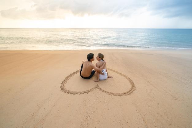 Para siedzi w sercu rysunek na piaszczystej plaży relaksujące opalanie.