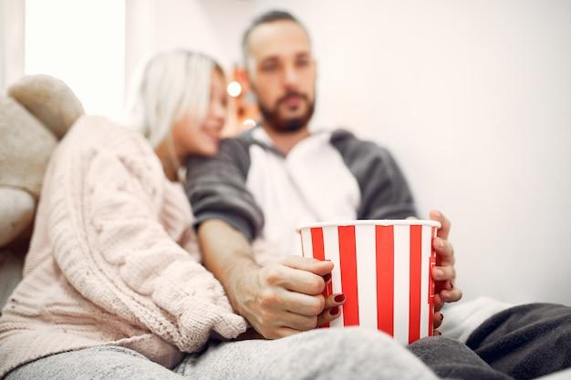 Para siedzi z miską popcornu