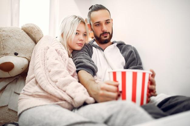 Para siedzi z popcornami i duży miś