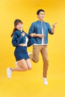 Para skacząca w powietrzu trzymając się za ręce, ciesząc się czasem razem na żółtym tle