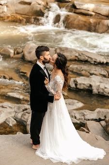Para ślub, kochankowie na tle kamiennej rzeki.