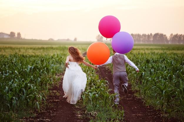 Para ślub na polu z dużymi balonami