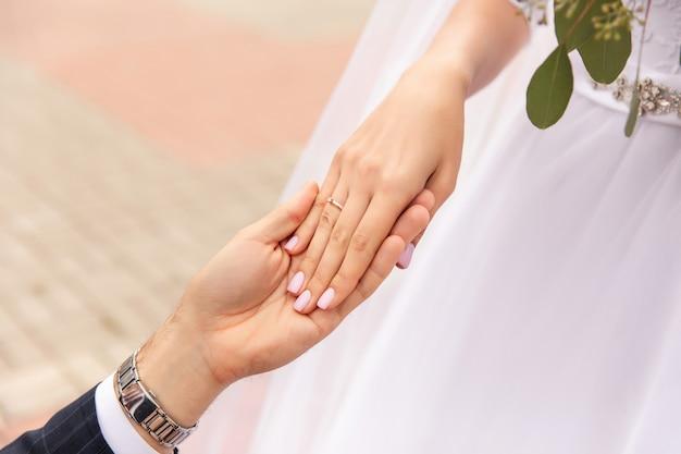 Para ślub, państwo młodzi, trzymając się za ręce, piękny dzień ślubu