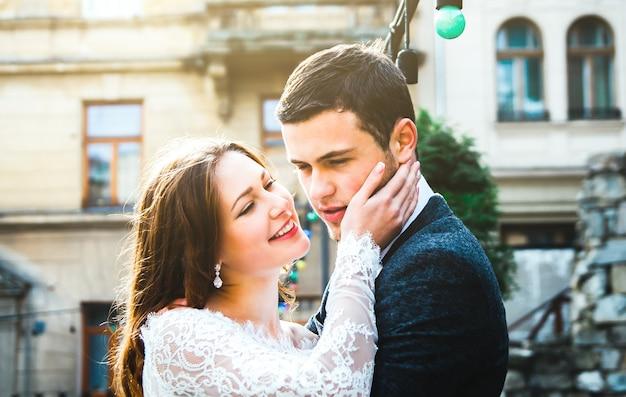 Para ślub przytula się na starym mieście. rustykalna panna młoda z rozpuszczonymi włosami trzyma twarz pana młodego w szarym garniturze i muszce. miłość w starożytnym średniowiecznym mieście. biała koronkowa suknia ślubna. zabytkowe detale architektoniczne.