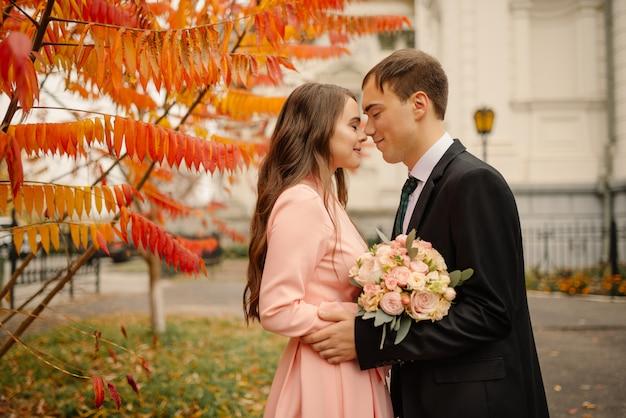 Para ślub przytula w starym mieście na jesieni. kamienne ściany starożytnego kościoła. romantyczna miłość w stylu vintage ulicy. gotycka katedra.