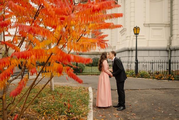 Para ślub przytula w starym mieście na jesieni. kamienne ściany starożytnego kościoła.