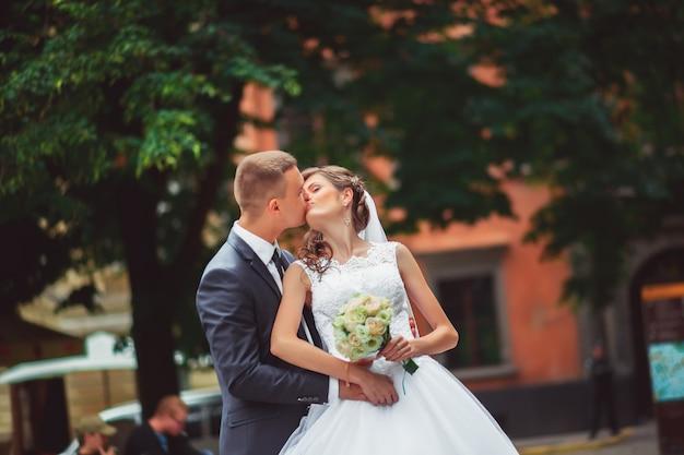Para ślub przytulanie i całowanie w bramie