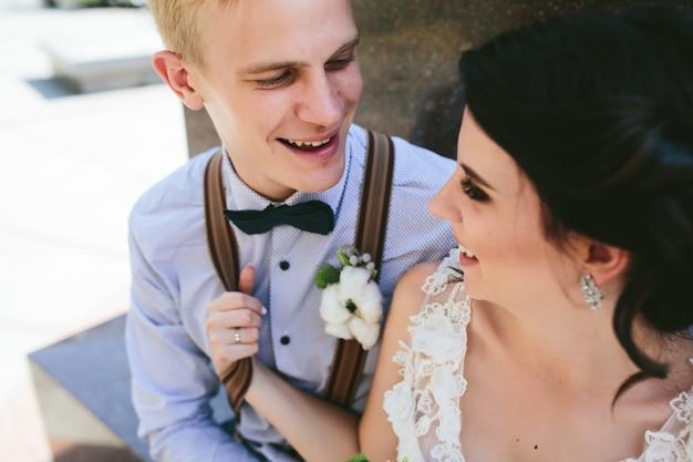 Para ślub siedzi na kamiennej ławce, zamknij widok