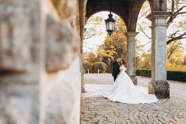 Para ślub spaceru w parku z zabytkowym pałacem.