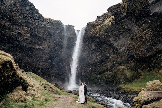 Para ślub stoi w pobliżu wodospadu na islandii