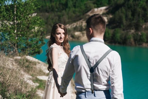 Para ślub stojąc na piaszczystym wzgórzu