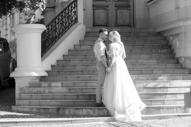 Para ślub w mieście w słoneczny letni dzień. panna młoda i pan młody przytulanie na schodach. czarny i biały