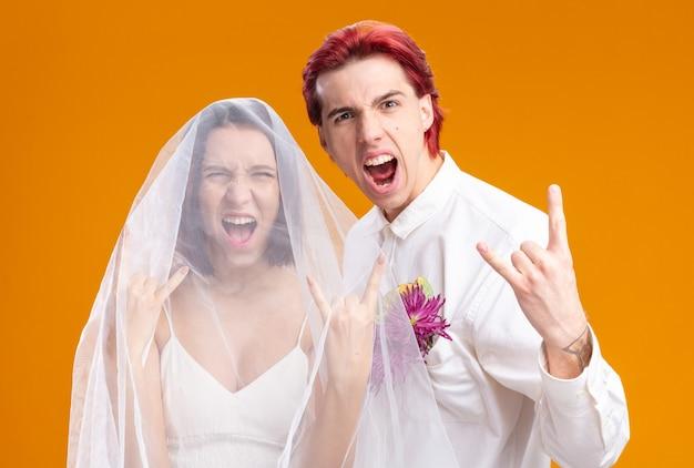 Para ślubna pana młodego i panny młodej w sukni ślubnej pozują razem wyglądając na szczęśliwych i podekscytowanych pokazując symbol rocka