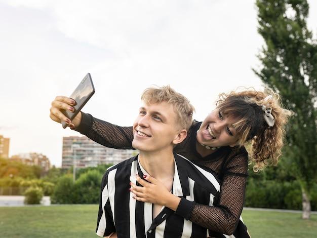 Para ślubna patrzeć na siebie, robić zdjęcia, szczęśliwa. w parku