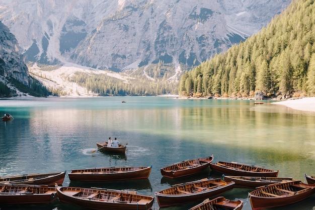 Para ślubna pływająca drewnianą łódką nad lago di braies we włoszech