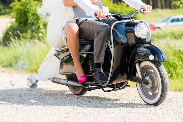 Para ślubna prowadząca skuter samochodowy w sukni i garniturze
