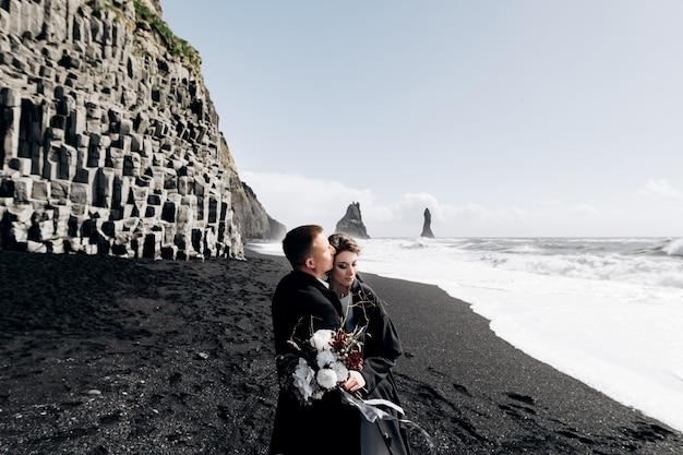 Para ślubna spaceruje po piaszczystej, czarnej plaży w vik w pobliżu bazaltowej skały