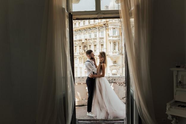 Para ślubna stoi na hotelowym balkonie z widokiem na stary budynek, przez otwarte okno.