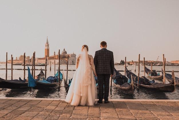 Para ślubna stoi na molo w wenecji
