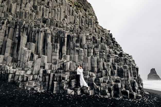 Para ślubna stoi na ścianie z kamiennych filarów, a państwo młodzi przytulają się do bazaltowego kekurs