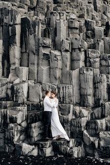 Para ślubna stoi na ścianie z kamiennych filarów, panna młoda i pan młody przytulają się na bazaltowych kekurach
