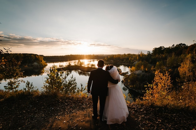 Para ślubna stoi nad jeziorem i patrzy na krajobraz