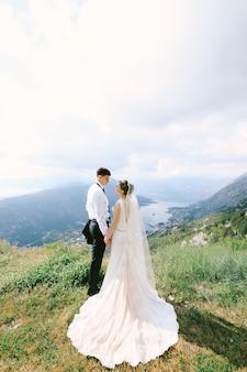 Para ślubna trzyma się za ręce na szczycie góry lovcen na tle zatoki kotorskiej
