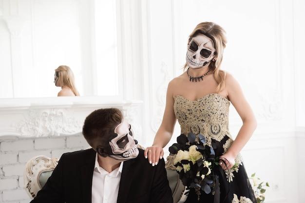Para ślubna ze szkieletem nadrabia halloween lub dzień zaduszny