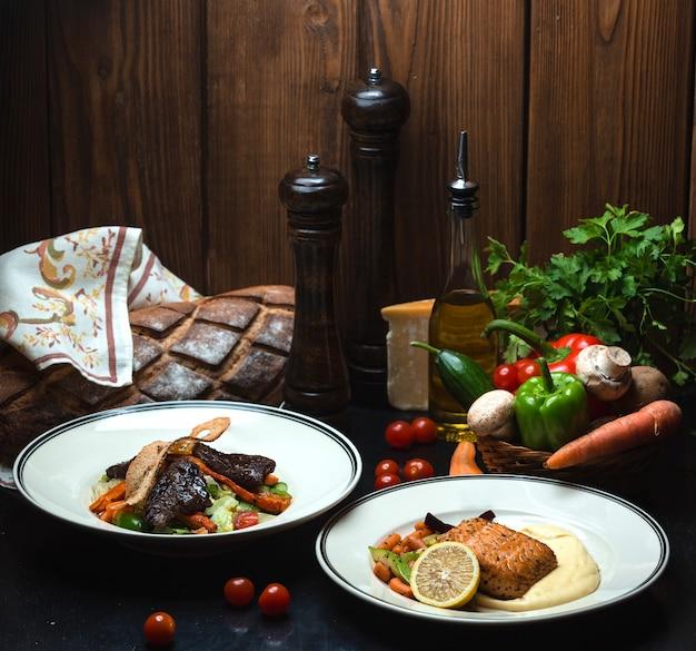 Para smażący mięso i łosoś na stole