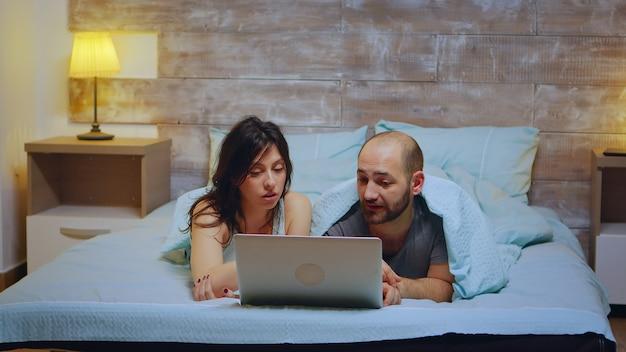 Para sobie piżamę leżąc w łóżku za pomocą laptopa na zakupy.