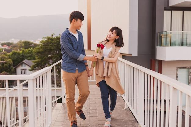 Para spaceru trzymając się różą