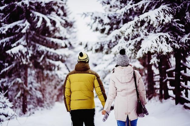 Para spaceru w zimowe ubrania wokół lasu ze śniegiem