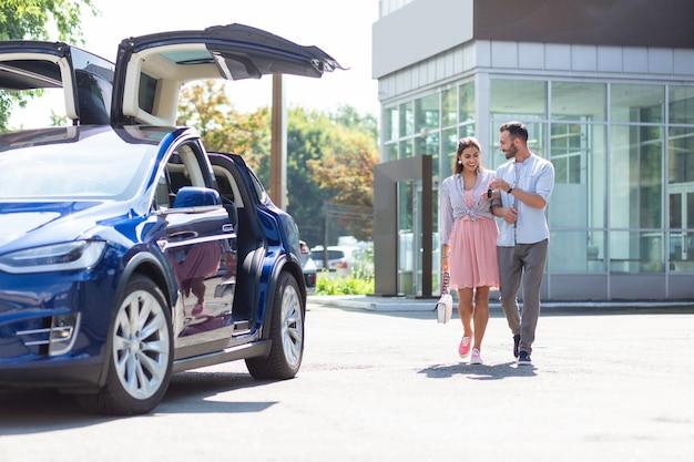Para spacerująca. kochająca, atrakcyjna para idąca do swojego ładnego luksusowego samochodu po wyjściu z biura