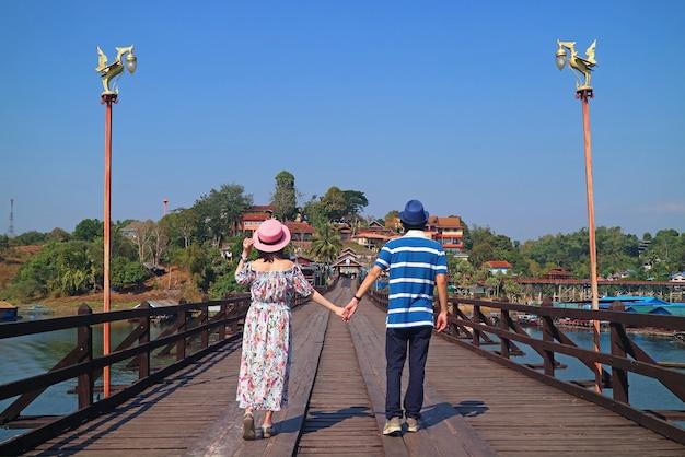 Para spacerująca ręka w rękę po moście mon bridge o długości 447 metrów, dystrykt sangkhlaburi, tajlandia
